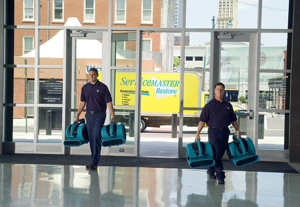 ServiceMaster techs entering a building in Merce